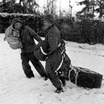 Two Sreaming Eagles drag airdropped supplies near Bastogne